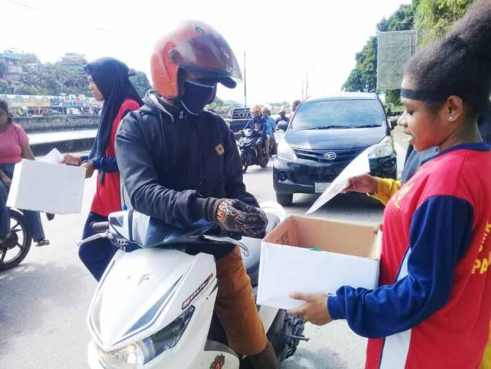Seorang pengemudi ojek memberikan donasi kepada siswi SMK Yapis Fakfak