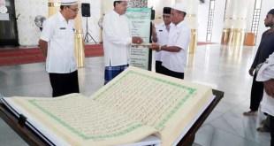 Bachtiar, kepala Dinas Sosial Kabupaten Fakfak, menyerahkan Al Qur'an akbar kepada Imam Masjid Baitul Makmur