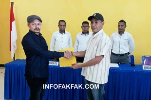 Ketua KPU Kabupaten Fakfak (kanan) menyerahkan berita acara penerimaan surst suara dan formulir kepada Ketua Bawaslu Kabupaten Fakfak